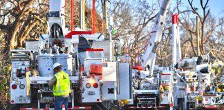 Lineworker behind line of bucket trucks restoring power