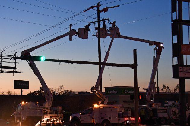 Evening restoration work of bucket trucks repairing power pole over traffic light